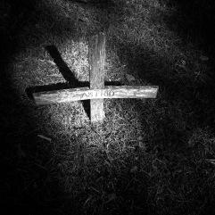 Wooden cross in dappled light