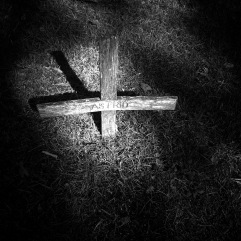 Wooden cross in dappled light