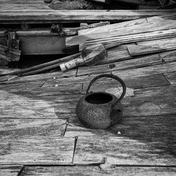 Rusty iron kettle on floorboards
